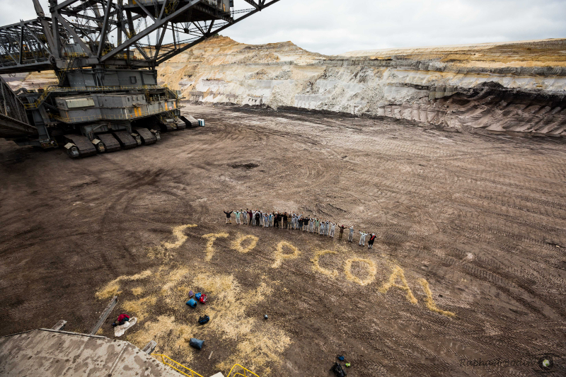 Underneath giant excavator: seemingly tiny people with an important message